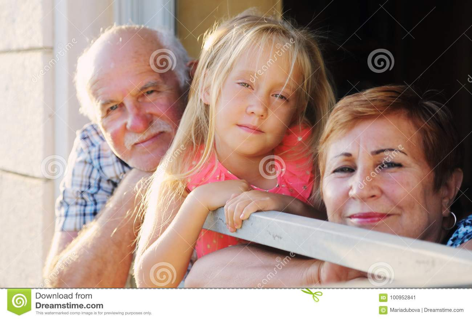 Дед и бабушка держа внучку