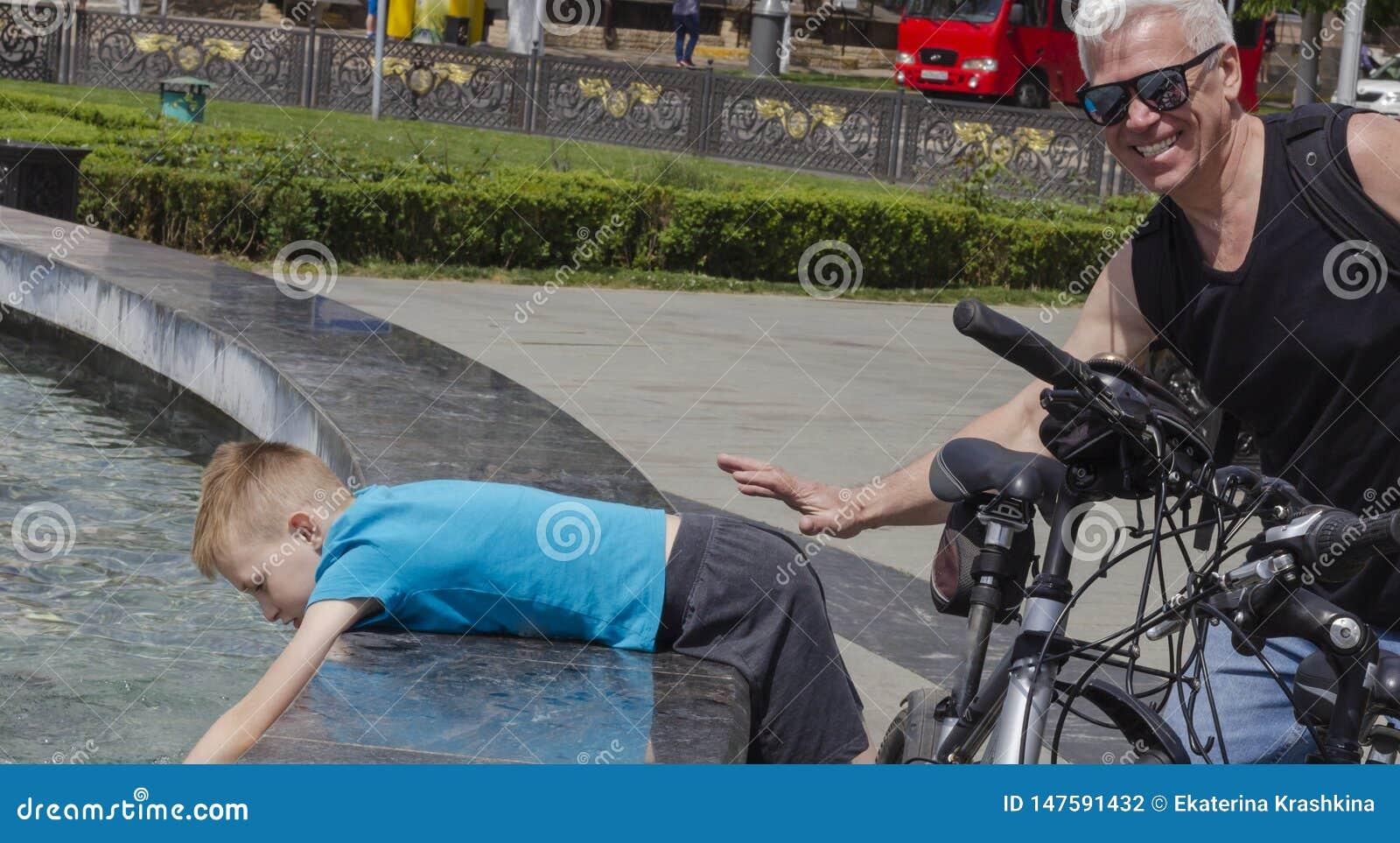 Дед и внук на совместной прогулке в парке около фонтана