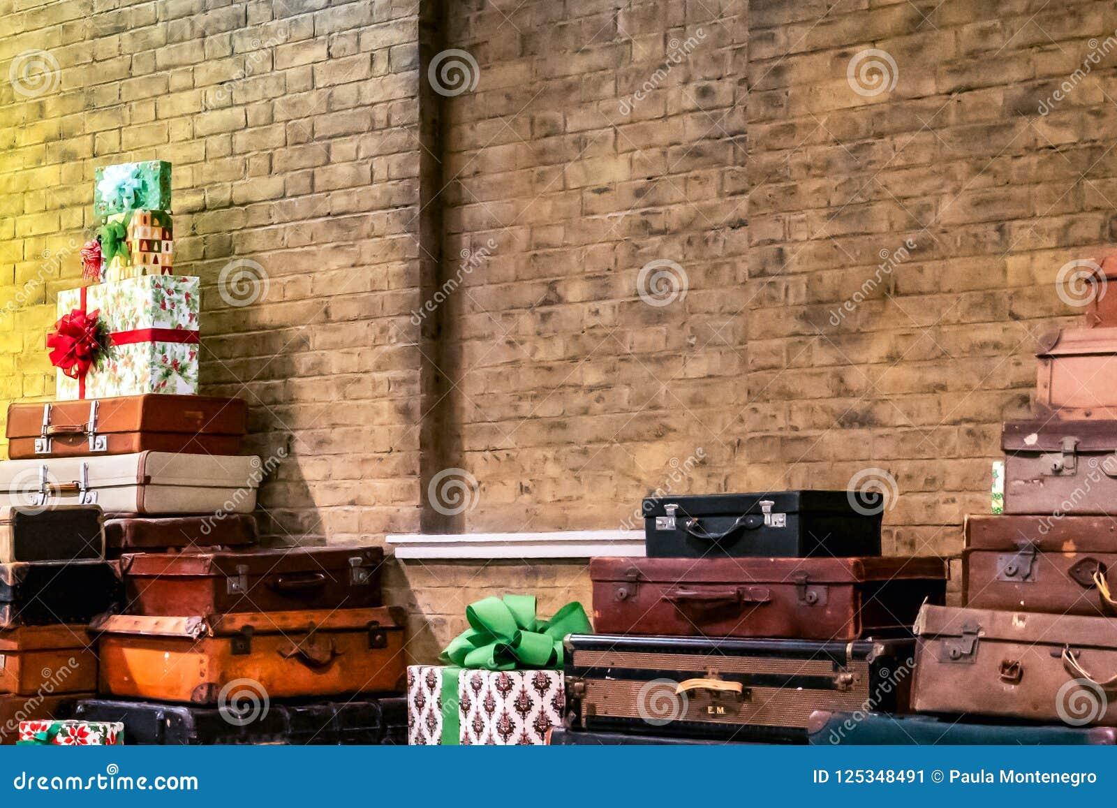 Декоративные винтажные чемоданы и подарки в кирпичной стене