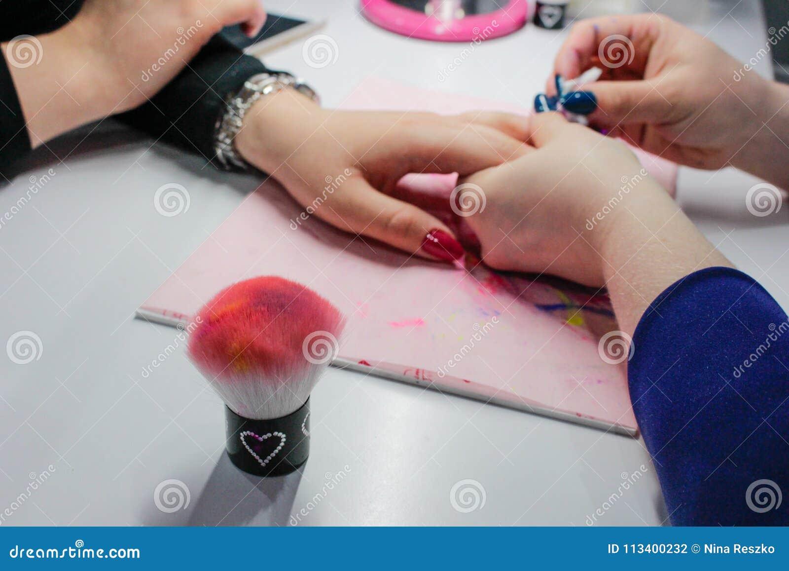 Делать краска ногтя, съемка крупного плана женщины в салоне ногтя получая маникюр beautician