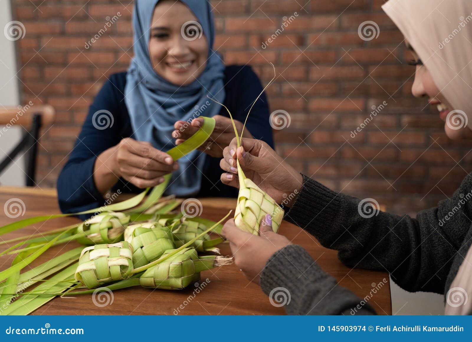 Делающ ketupat традиционную индонезийскую еду совместно