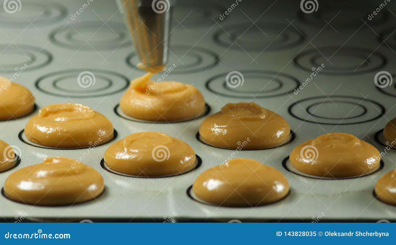 Делающ macaron, французский десерт, сжимая форму теста варя сумку Пищевая промышленность, масса или объем продукции