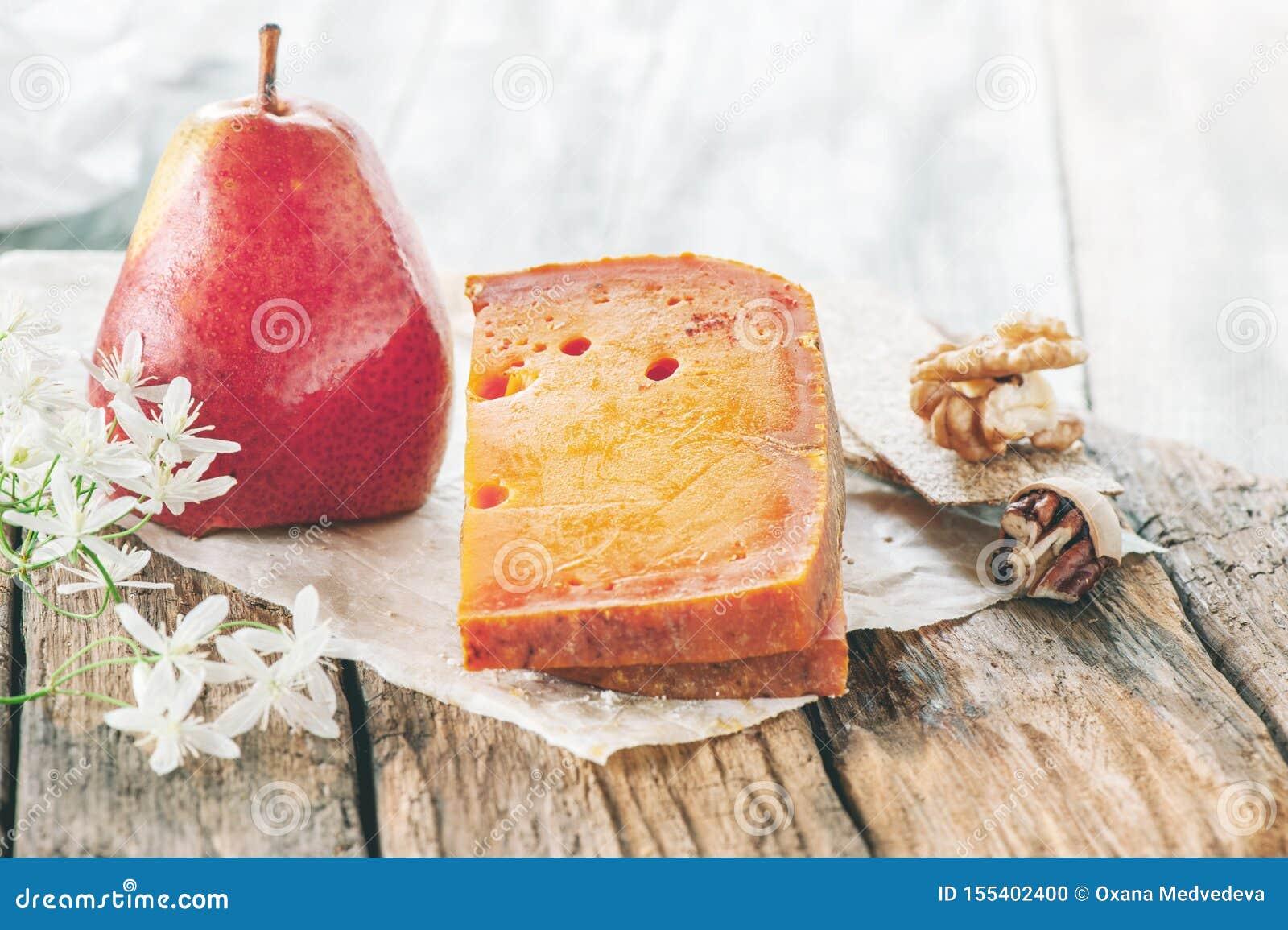 Деликатесы, пряные сыры Красный чеддер, на красивой текстурированной деревянной предпосылке с грушей смачная закуска для гурманов