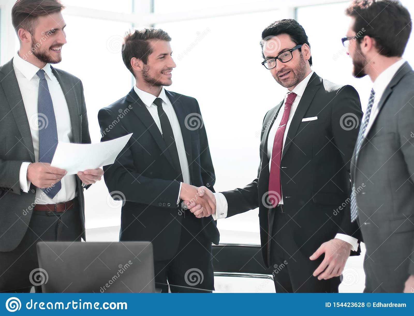 Деловые партнеры рукопожатия стоя в офисе