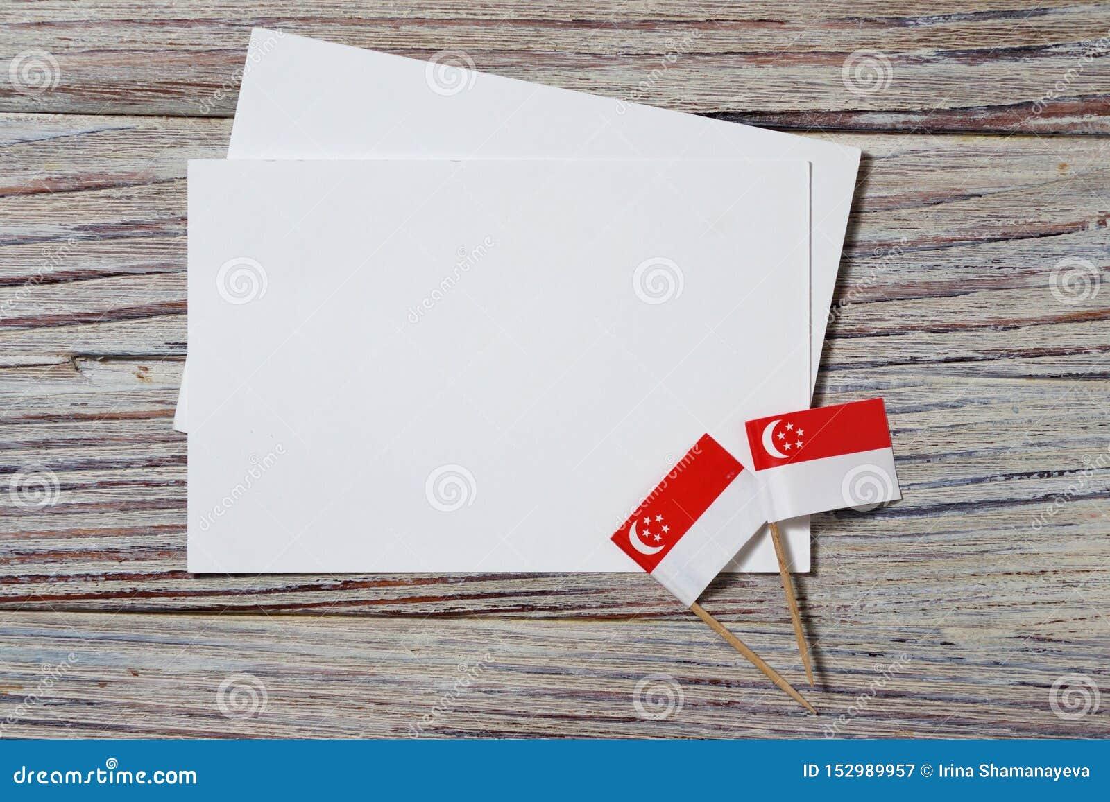 День независимости Сингапура 9-ое августа концепция свободы, независимости и патриотизма мини флаги с листами белой бумаги дальше