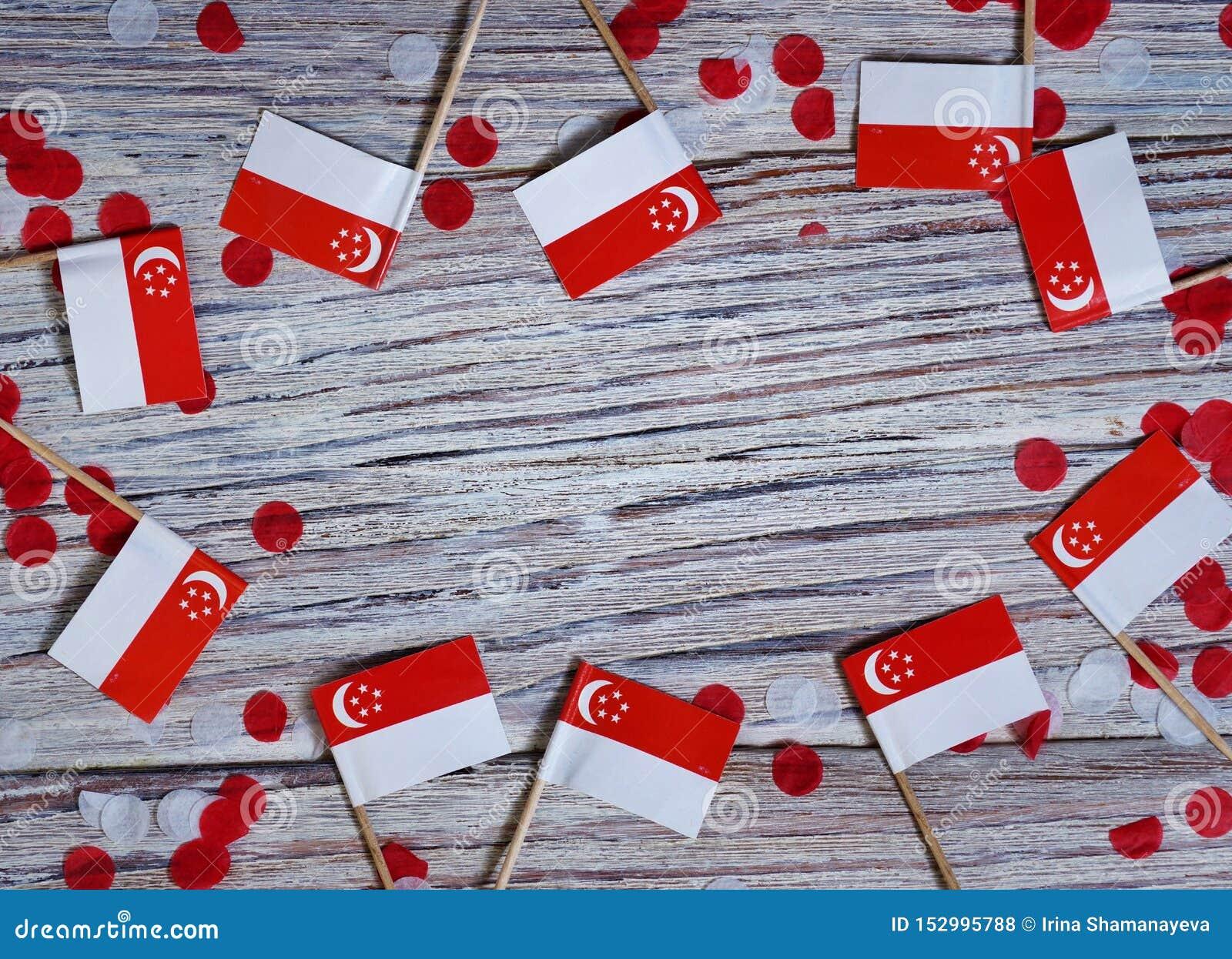 День независимости Сингапура 9-ое августа концепция свободы, независимости и патриотизма мини флаги с confetti на деревянном