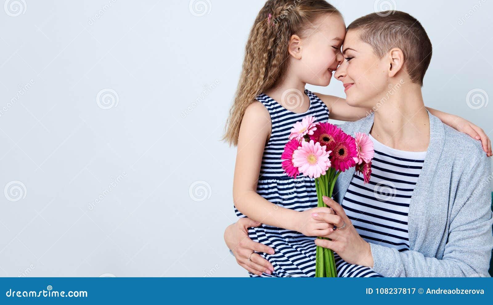День счастливого ` s дня, женщин ` s матери или предпосылка дня рождения Милая маленькая девочка давая букет мамы розовых маргари