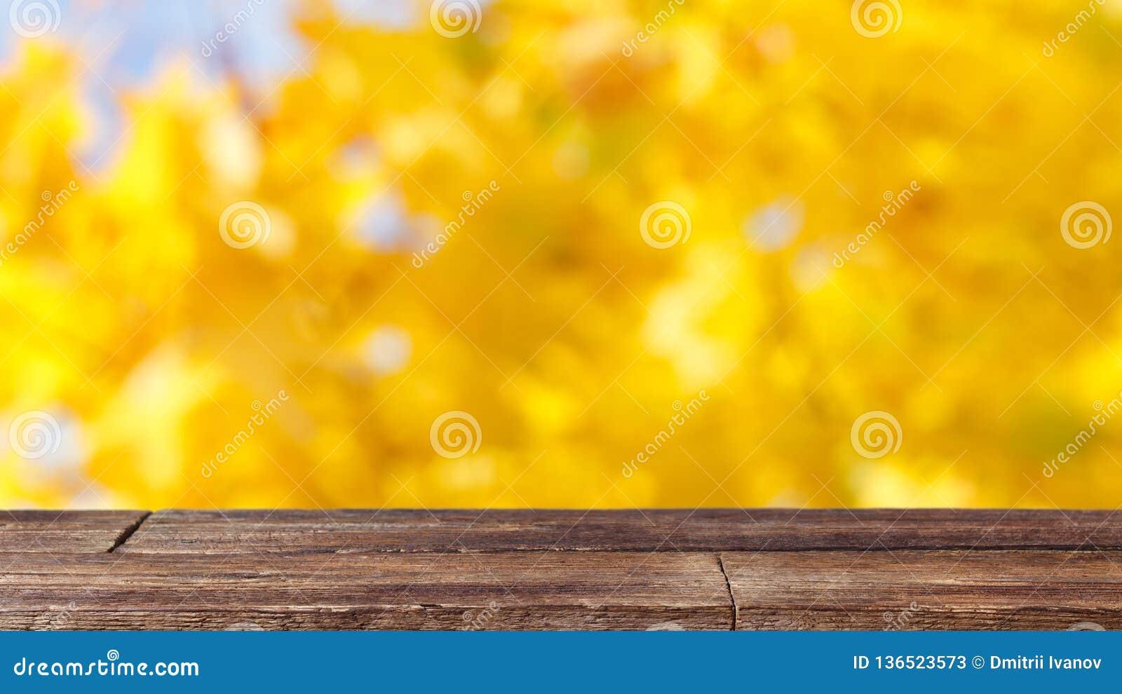 Деревенская деревянная таблица на предпосылке желтого bokeh абстрактной