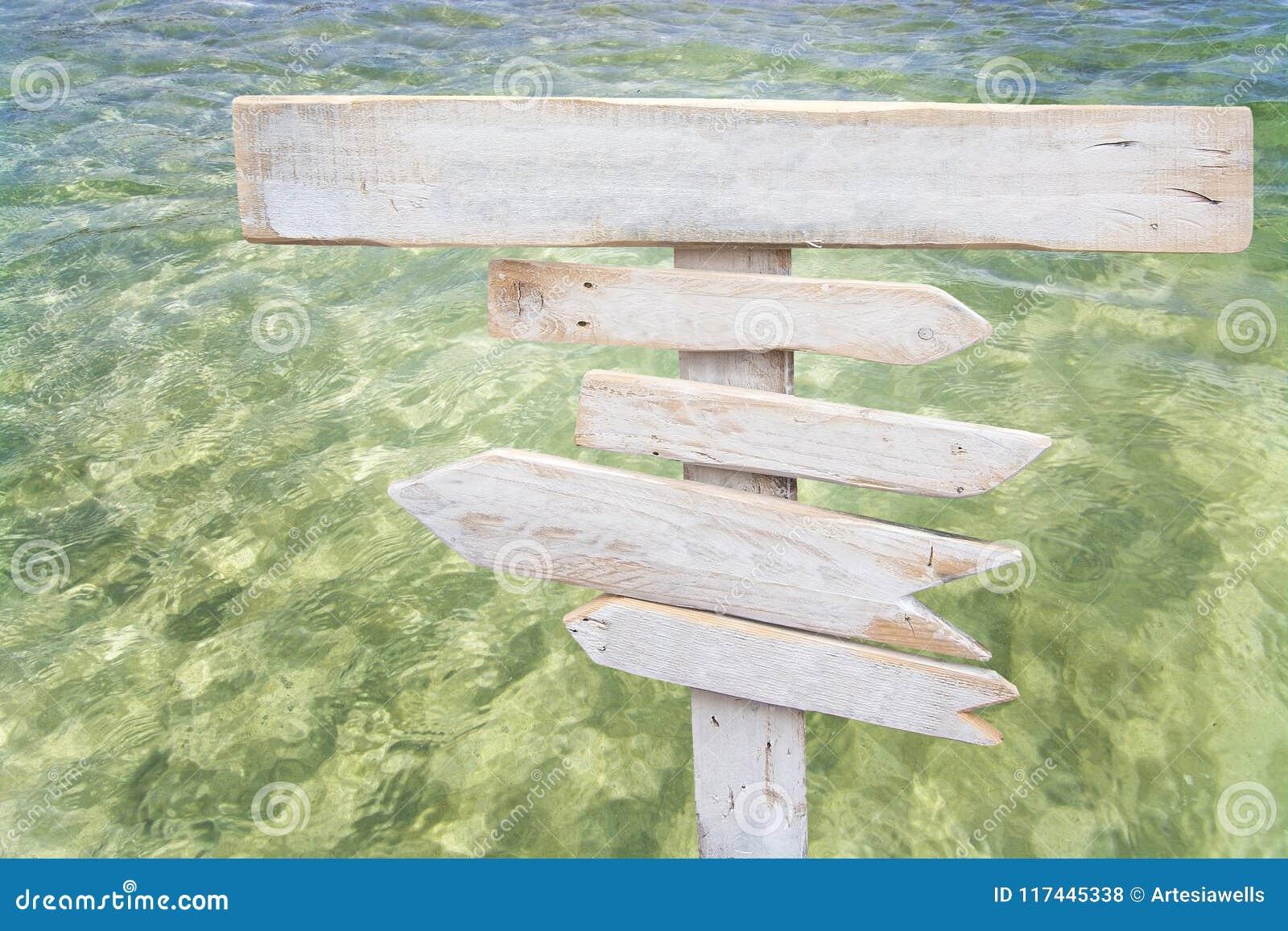 Деревенские белые пустые центризованные деревянные подписывают сверх свежую зеленую воду океана