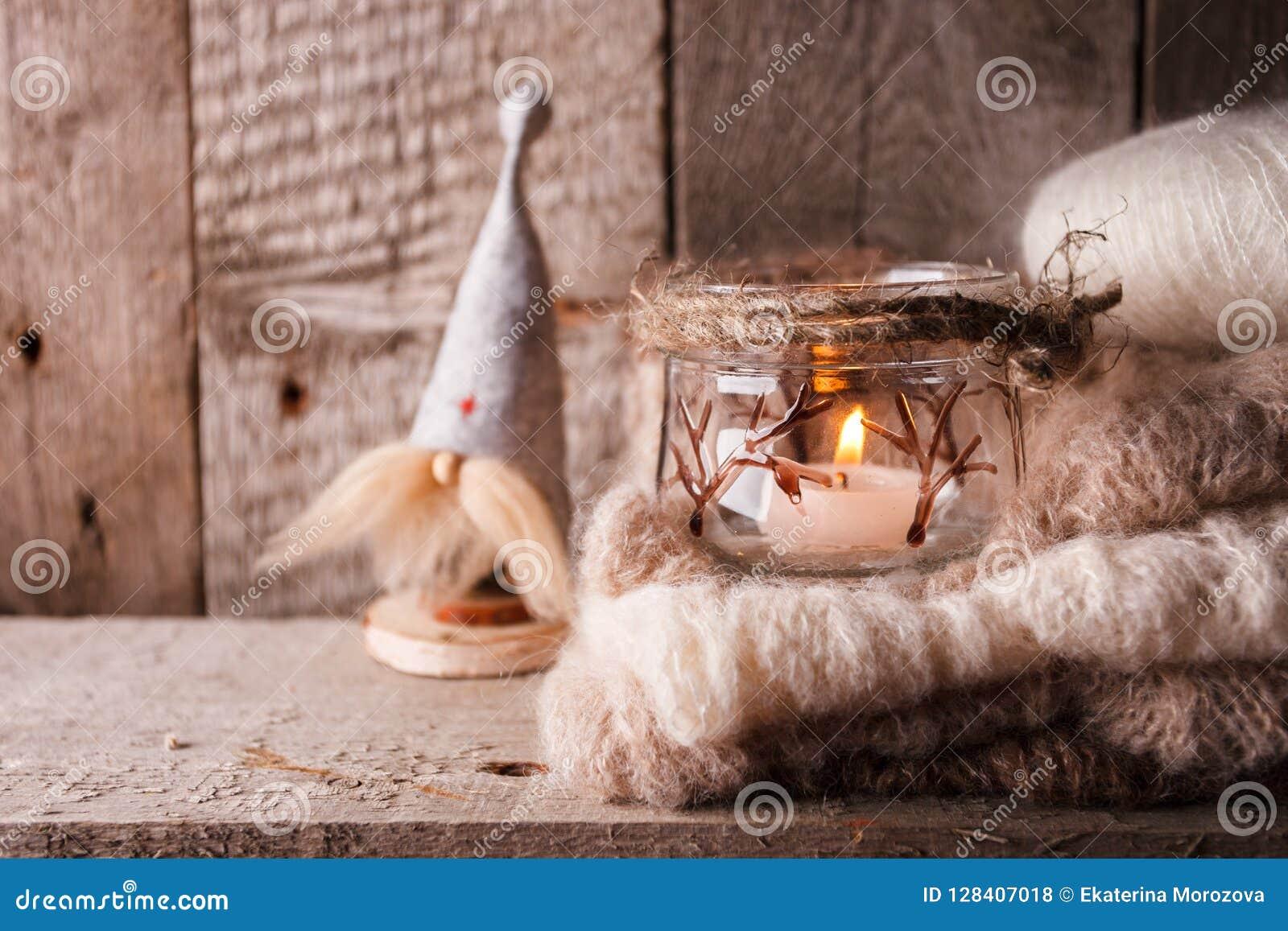 Деревенское decoraton с handmade внутренним гномом игрушки, свечой и греет связанный шарф на коричневой деревянной предпосылке, с