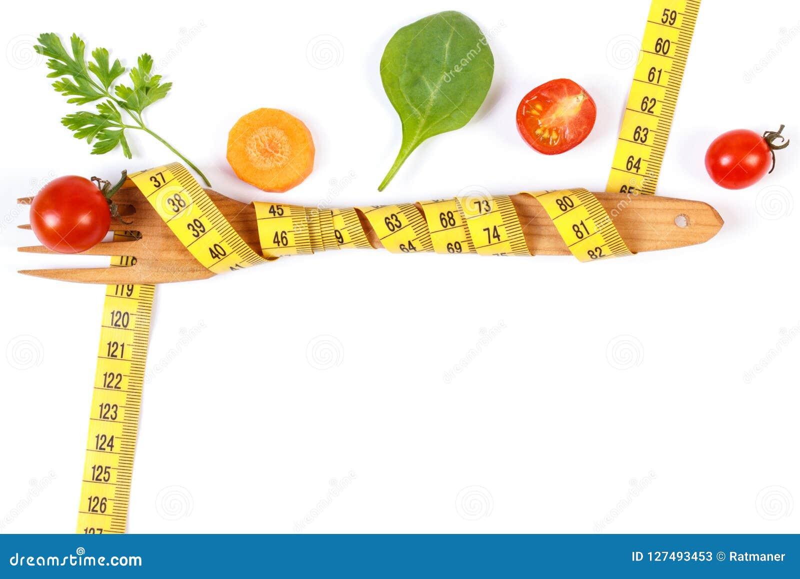 Деревянная вилка обернула сантиметр и свежие овощи, концепция теряют вес и здоровое питание