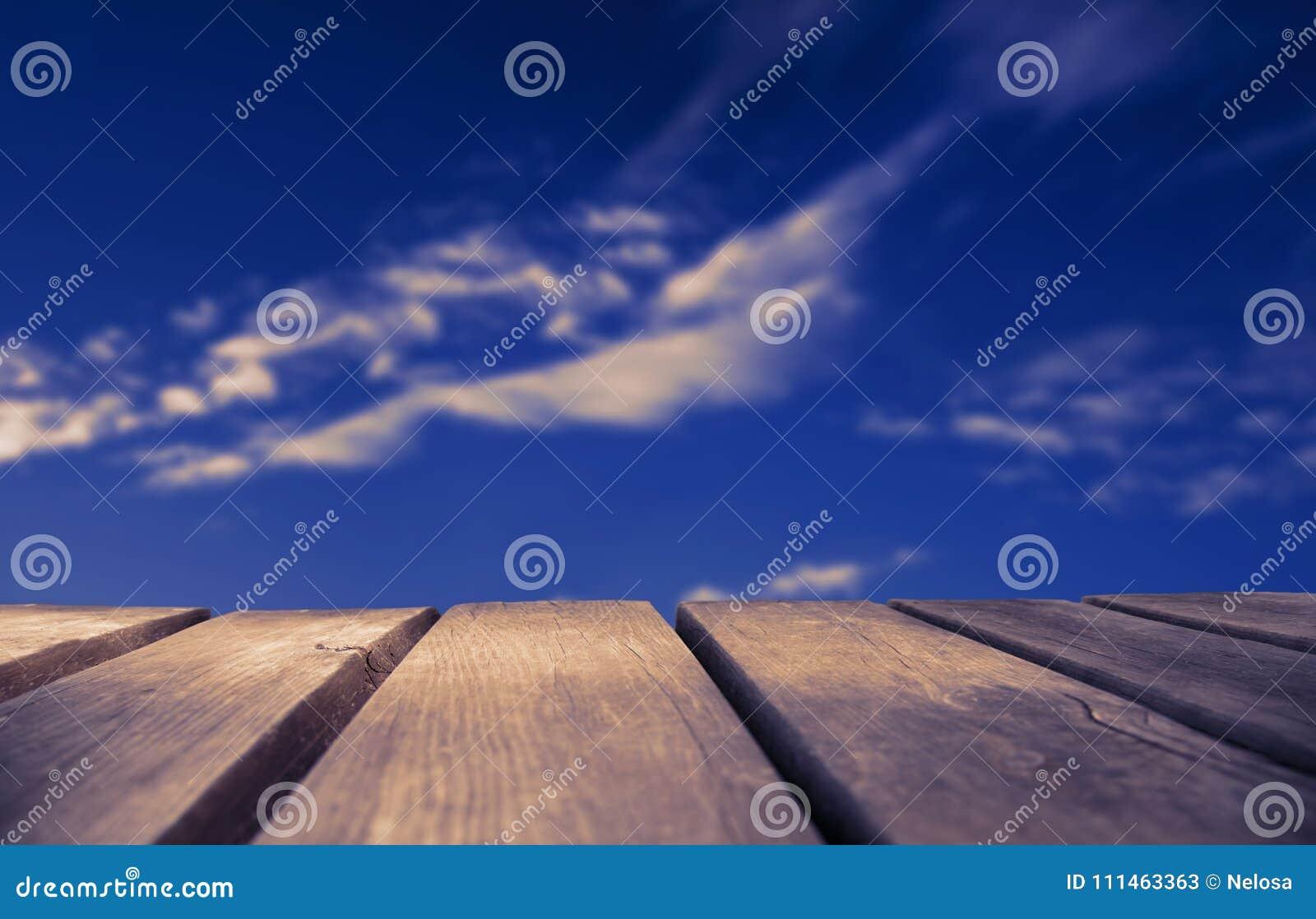 Деревянная доска с голубым небом как предпосылка, рубиновый ретро фильтр