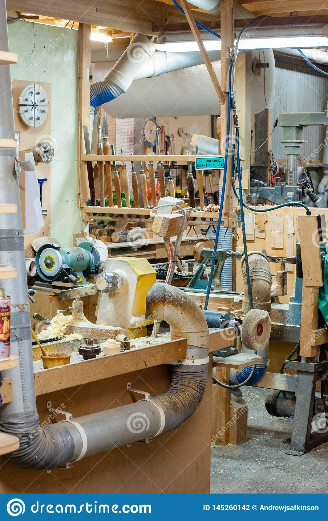 Деревянная мастерская с пылью и shavings, инструментами и машинным оборуд