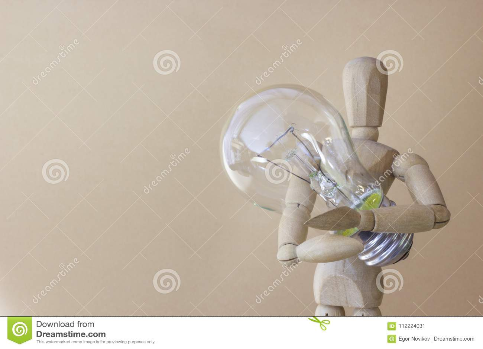 Деревянная персона держит электрическую лампочку в руке