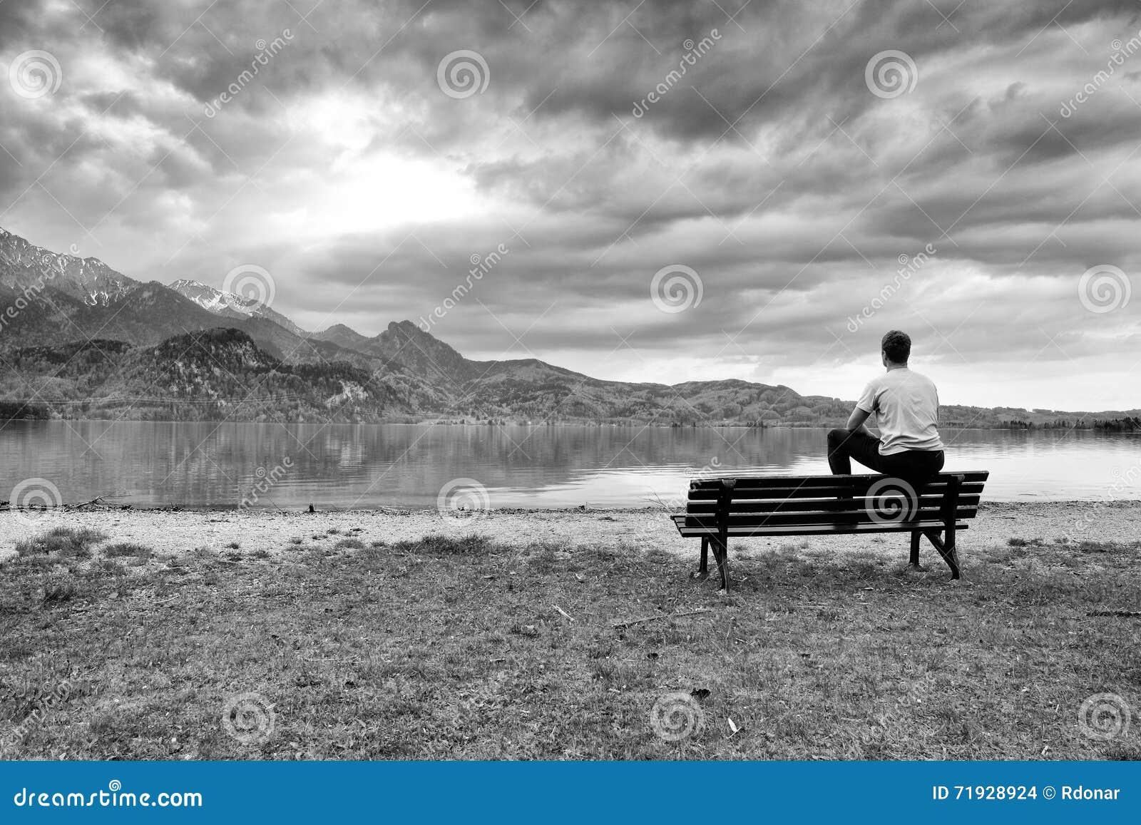 Деревянная скамья для ослаблять на береге Взгляд на горах Альпов с белым зеркалом пиков