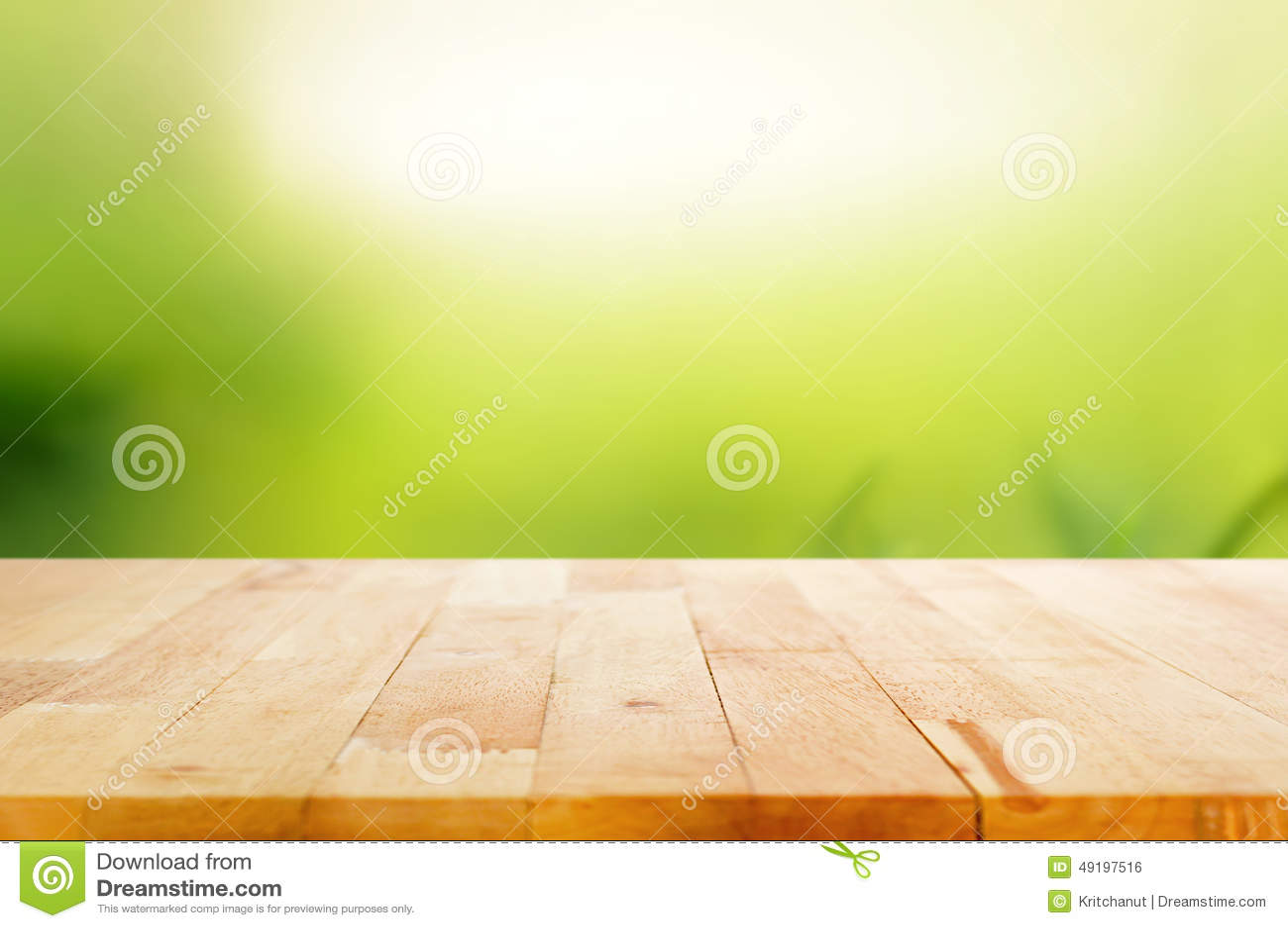 Деревянная столешница на абстрактной предпосылке зеленого цвета природы