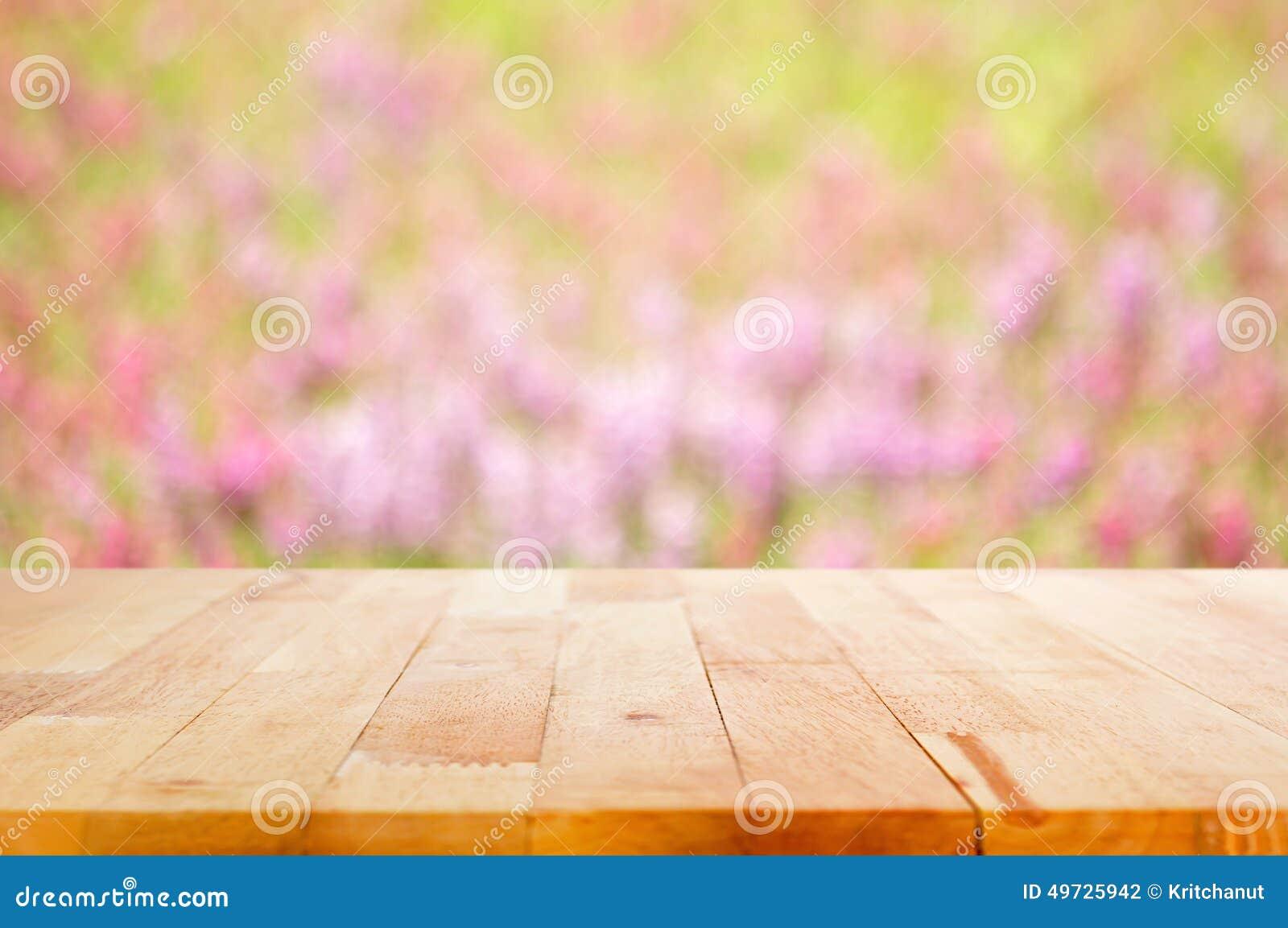 Деревянная столешница на предпосылке цветочного сада нерезкости