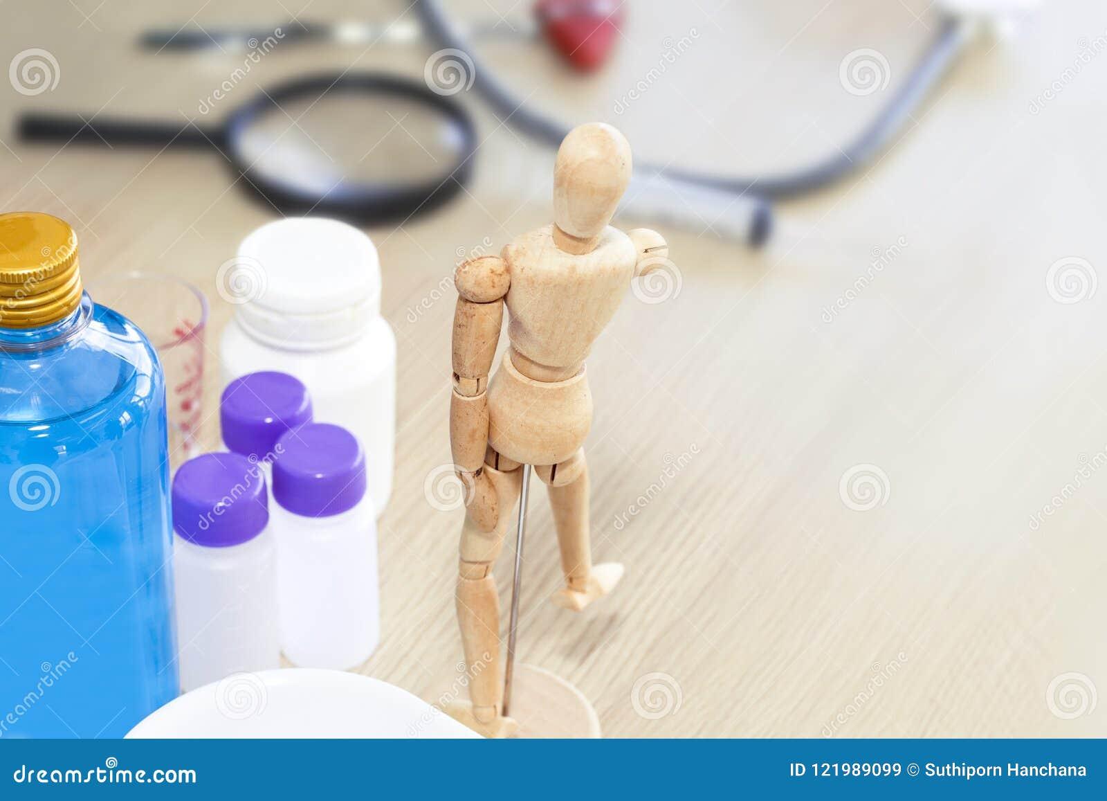 Деревянная человеческая модель, спирт затирания и медицинское оборудование на таблице