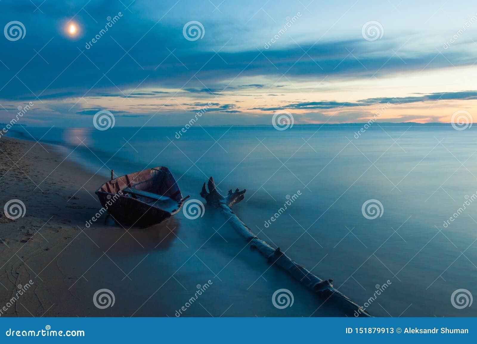 Деревянная шлюпка на береге Lake Baikal в лунном свете в вечере
