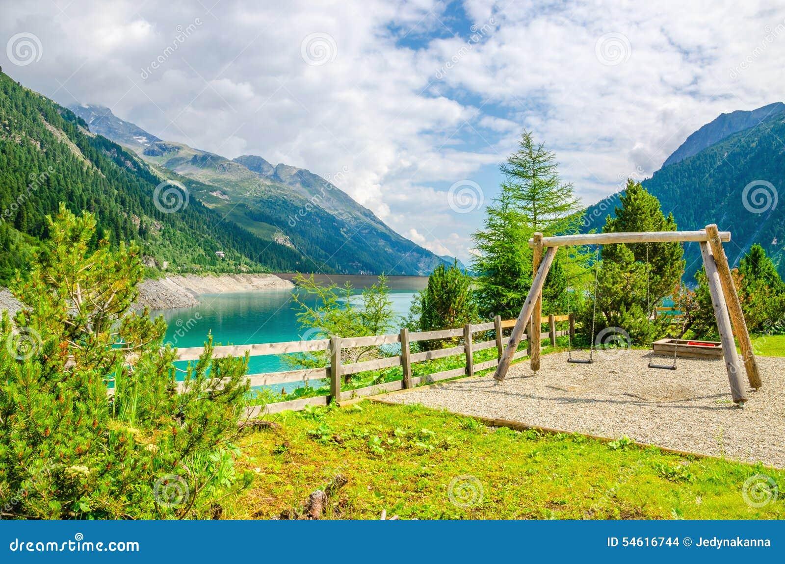 Деревянное качание с лазурным озером горы, Австрией