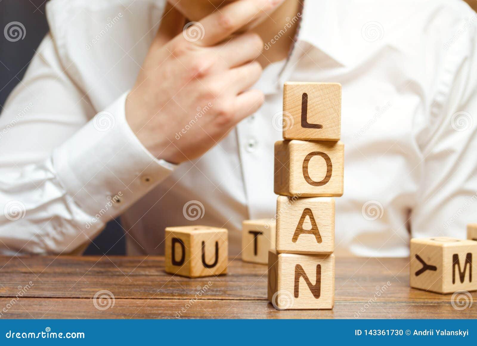 Деревянные блоки с займом и бизнесменом слова Заем потребителя, банка и свойства Дело и предпринимательское развитие