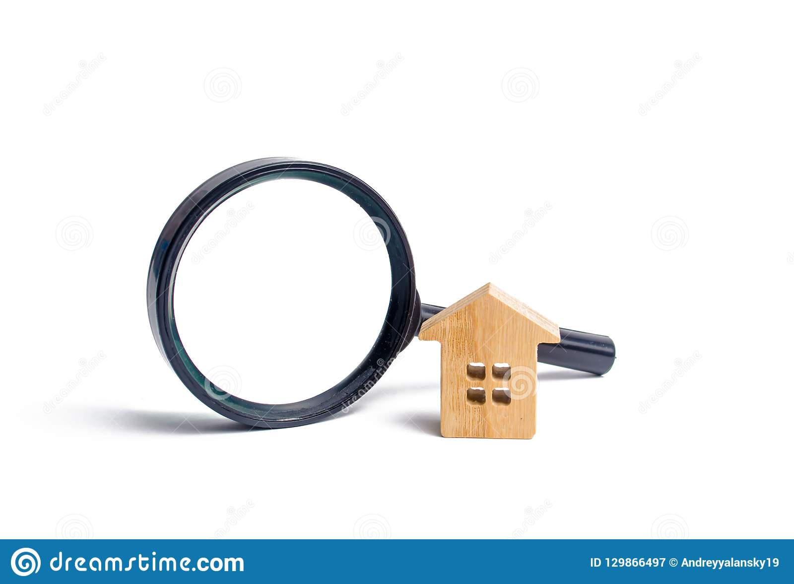 Деревянные дом и лупа на белой предпосылке Покупающ и продающ недвижимость, строя новые здания, офисы и дома