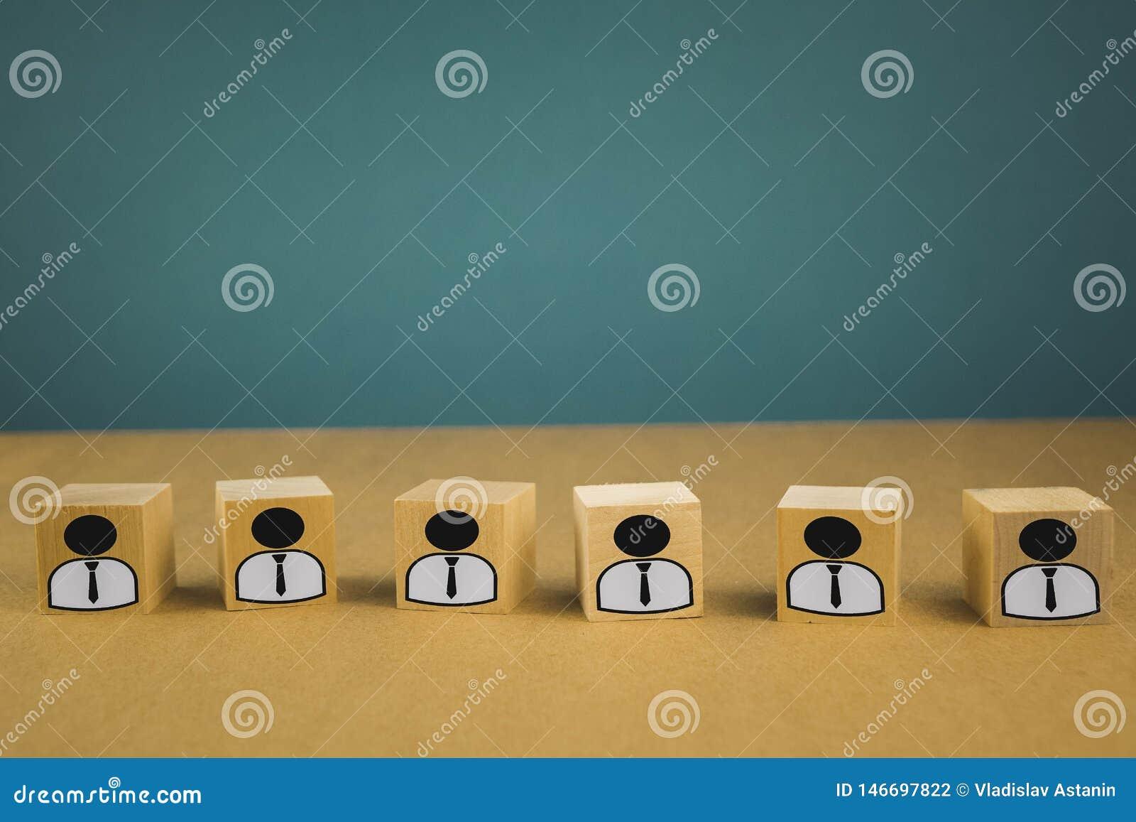 деревянные кубы стоя в ряд, значащ работников зарплаты стоя в одной линии, абстракция на голубой предпосылке