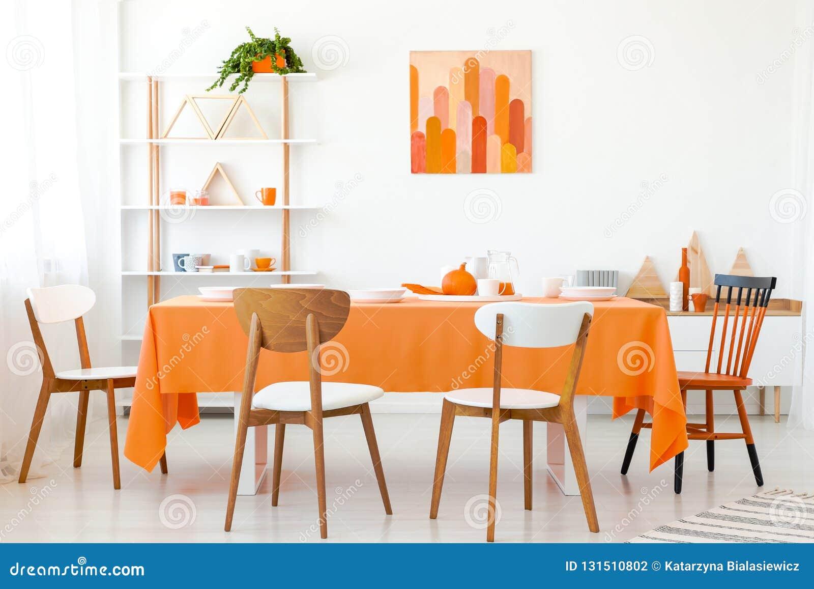 Деревянные стулья на оранжевой таблице в белой столовой