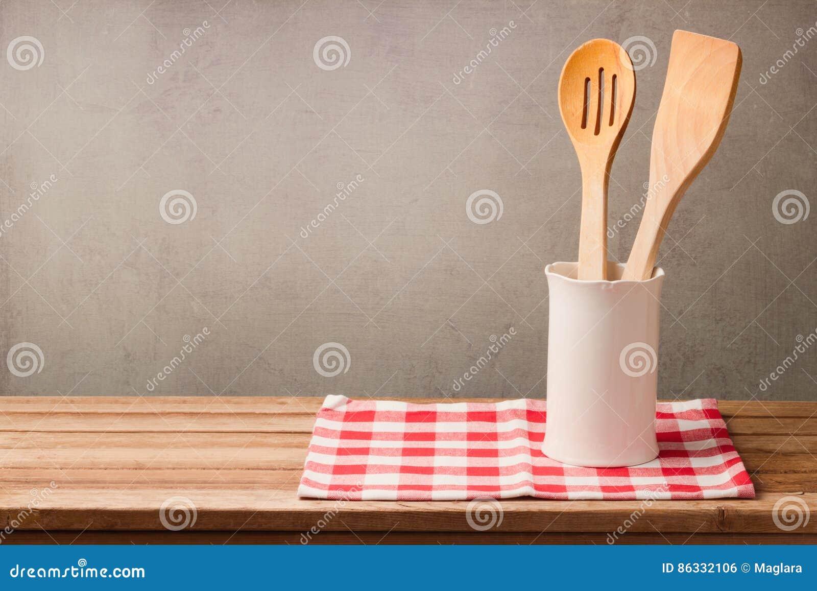 Деревянные утвари кухни на таблице с скатертью над grunge огораживают предпосылку с космосом экземпляра для монтажа продукта