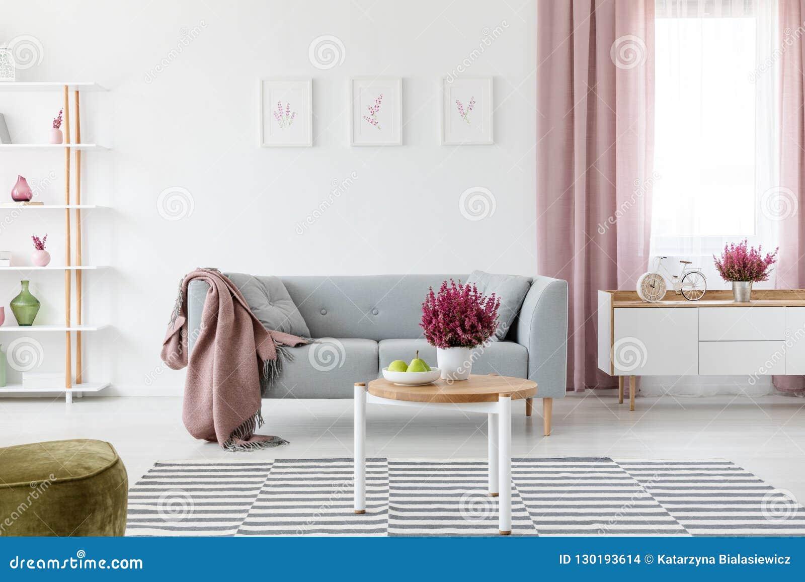 Деревянный журнальный стол со свежими вереском и плодами на плите на реальном фото яркой гостиной внутреннем с плакатами на стене