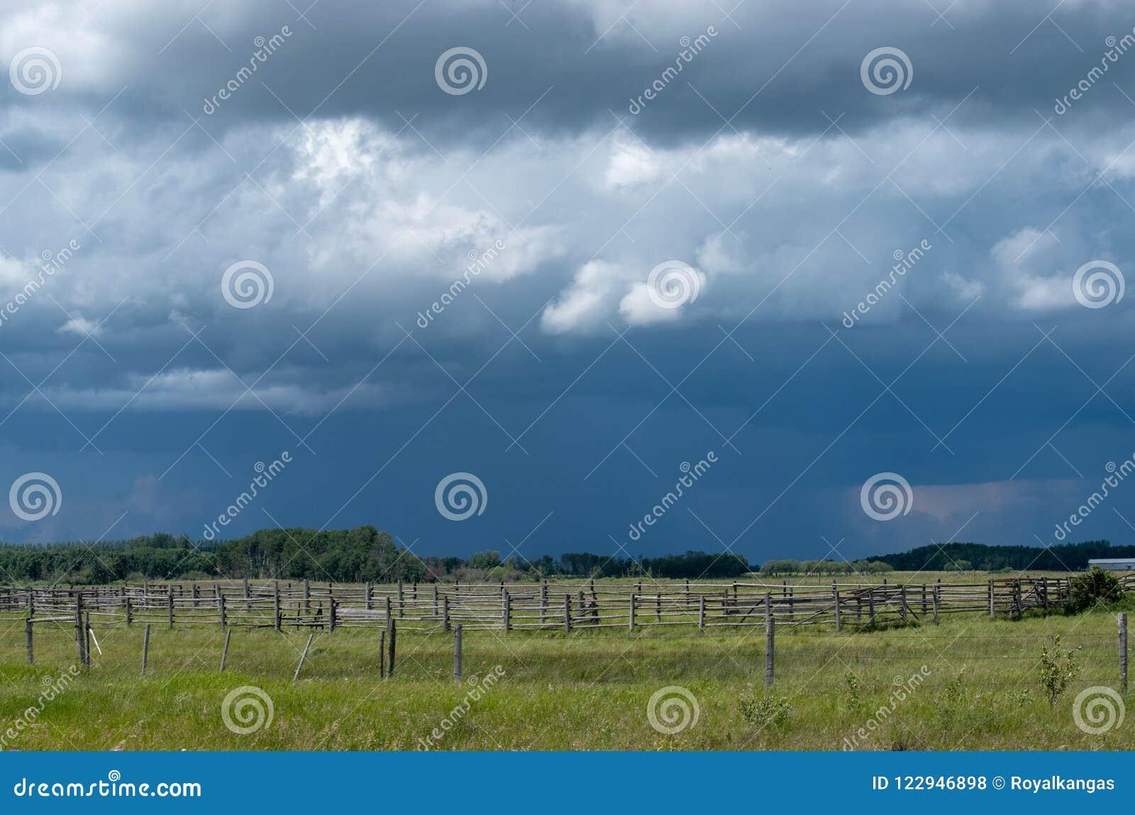 Деревянный загон с причаливая облаками шторма, Саскачеван, Канада
