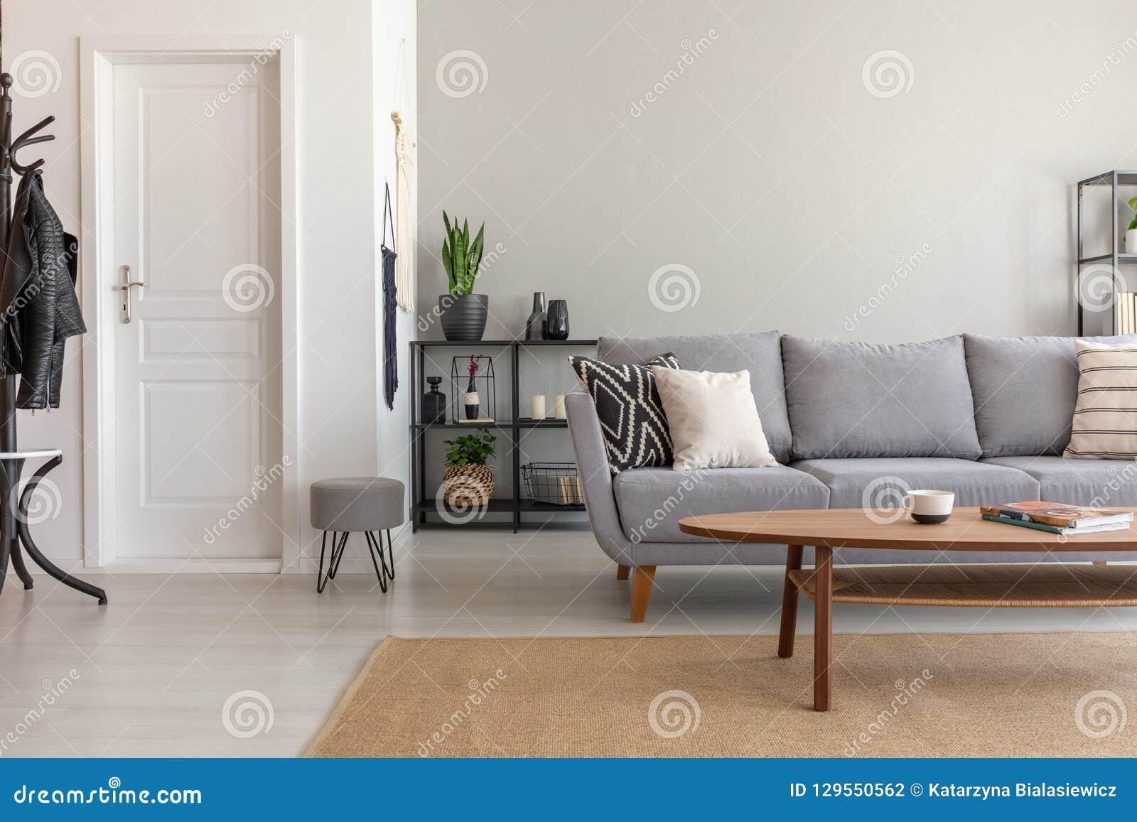 Деревянный стол на ковре перед серой софой в минимальной живущей комнате внутренней с дверью
