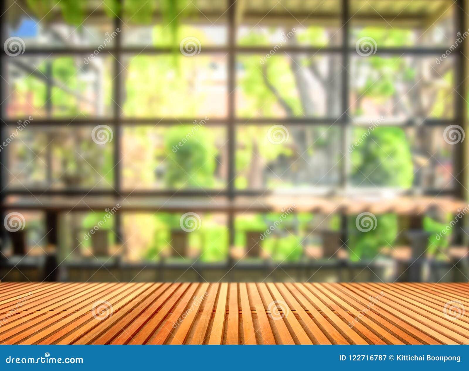 Деревянный стол перед запачканной предпосылкой кофейни