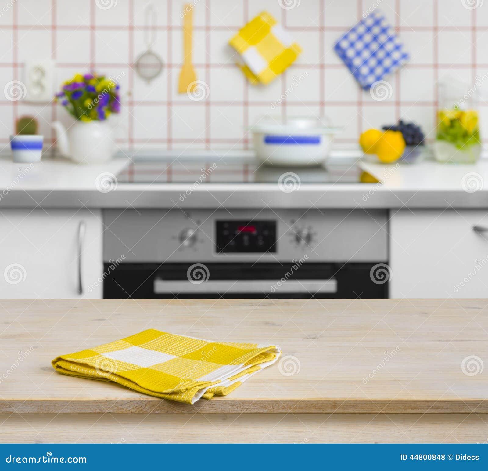 Деревянный стол с желтой салфеткой на предпосылке кухни