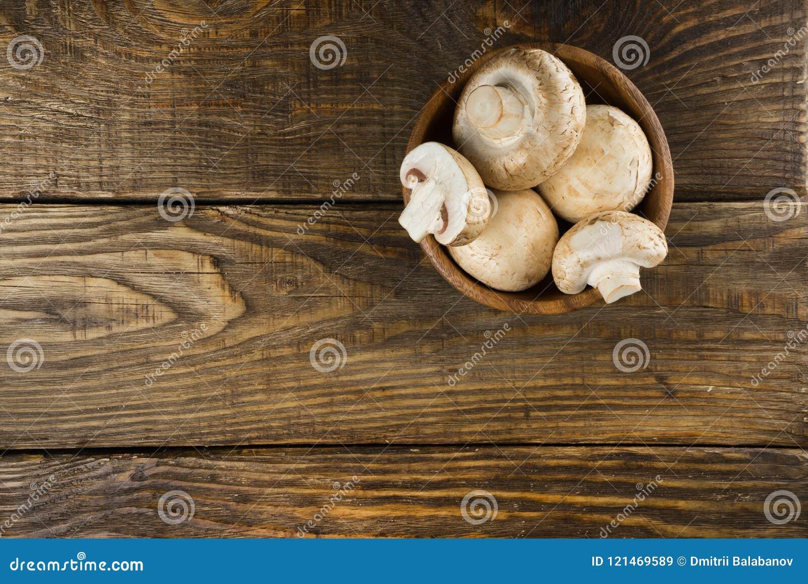 Деревянный шар с белыми champignons на деревянном столе Взгляд сверху