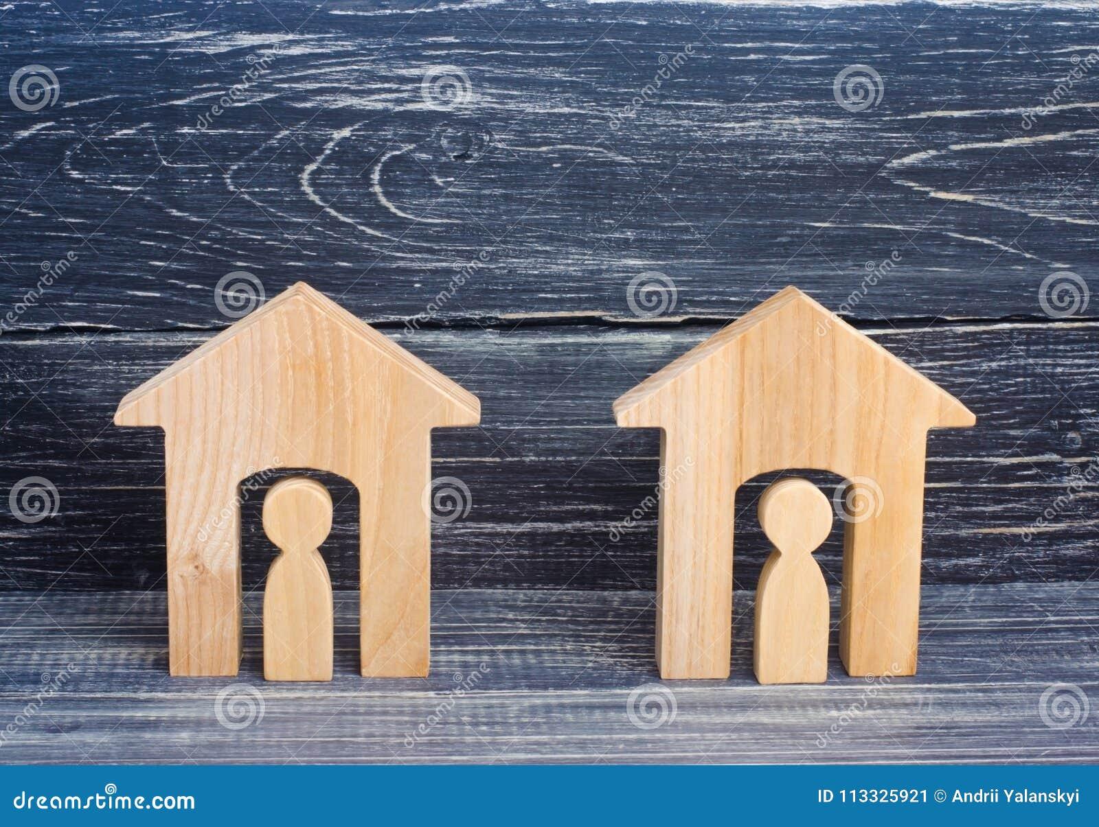 2 деревянных дома с людьми на черной предпосылке Концепция района, своих соседей Хорош-соседские отношения позволяет