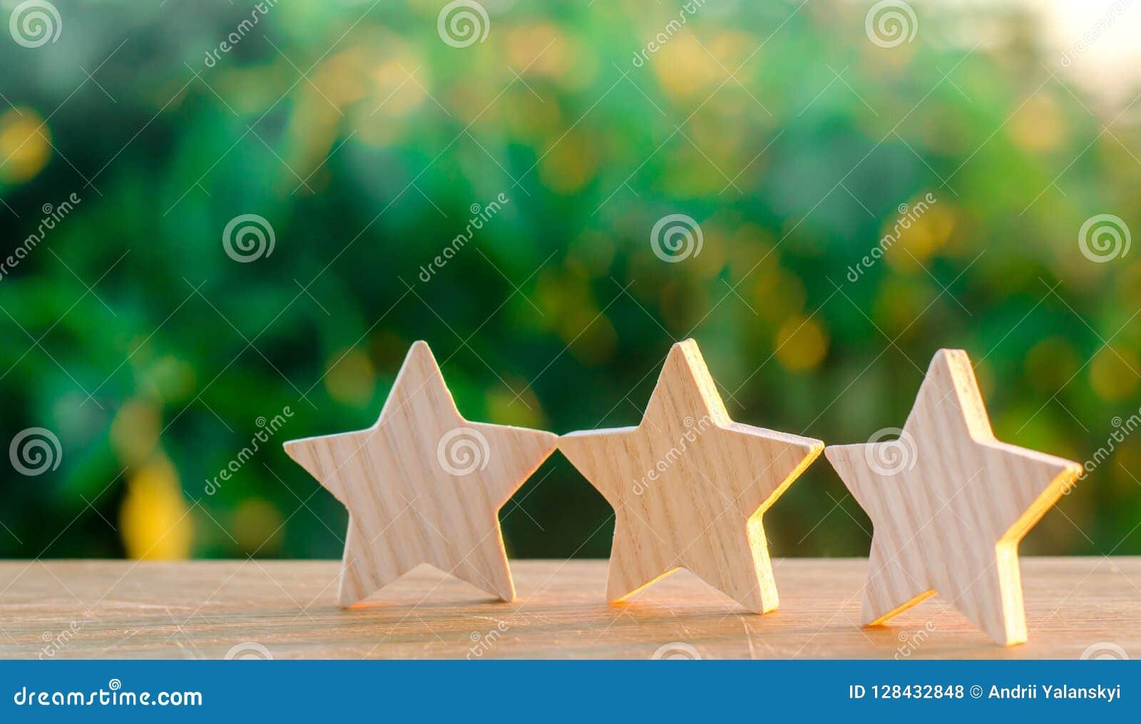 3 деревянных звезды на предпосылке зеленой предпосылки bokeh Концепция оценки гостиниц и ресторанов, оценки
