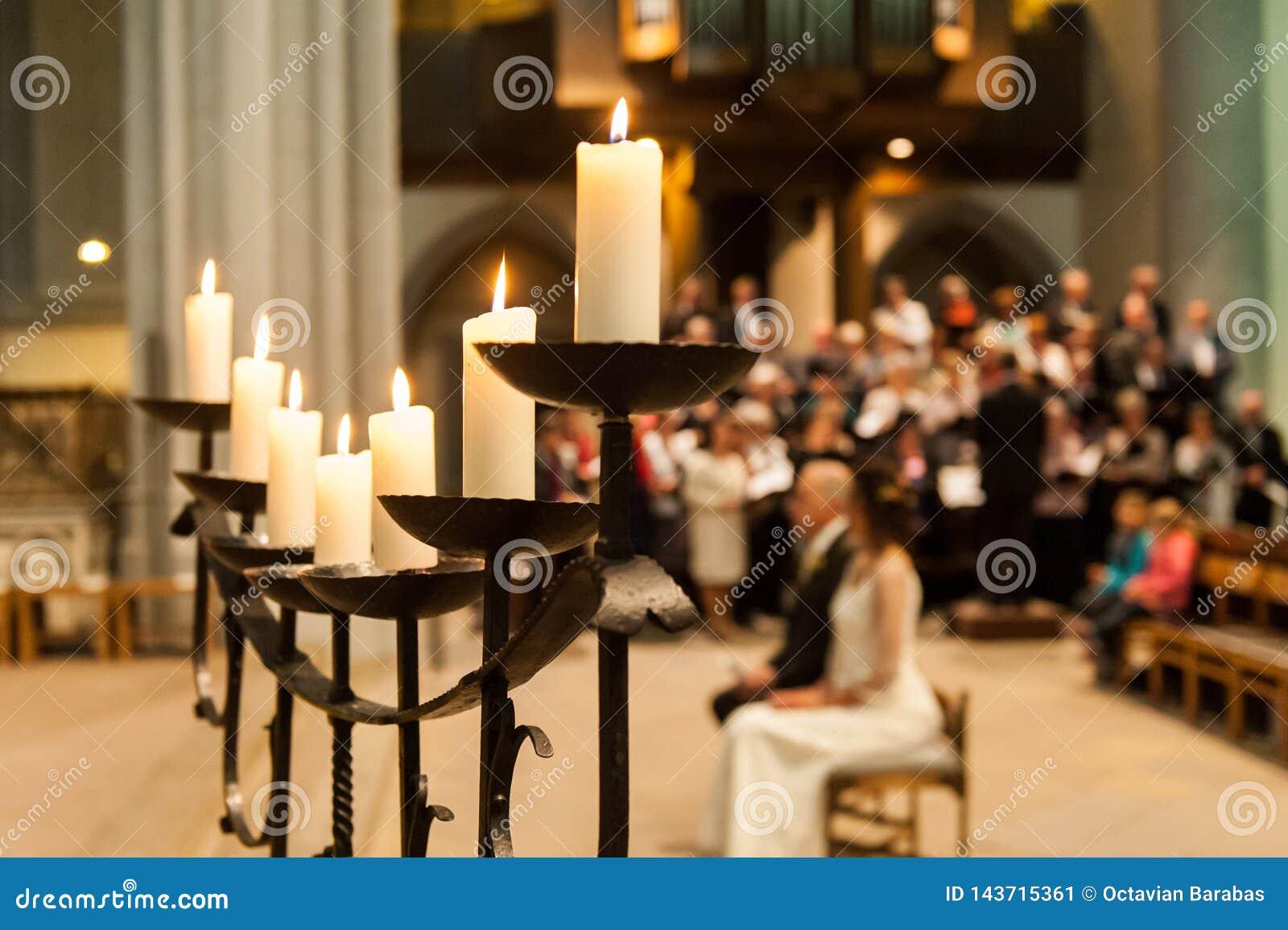 Держатель для свечи со свечами и запачканными людьми в церков