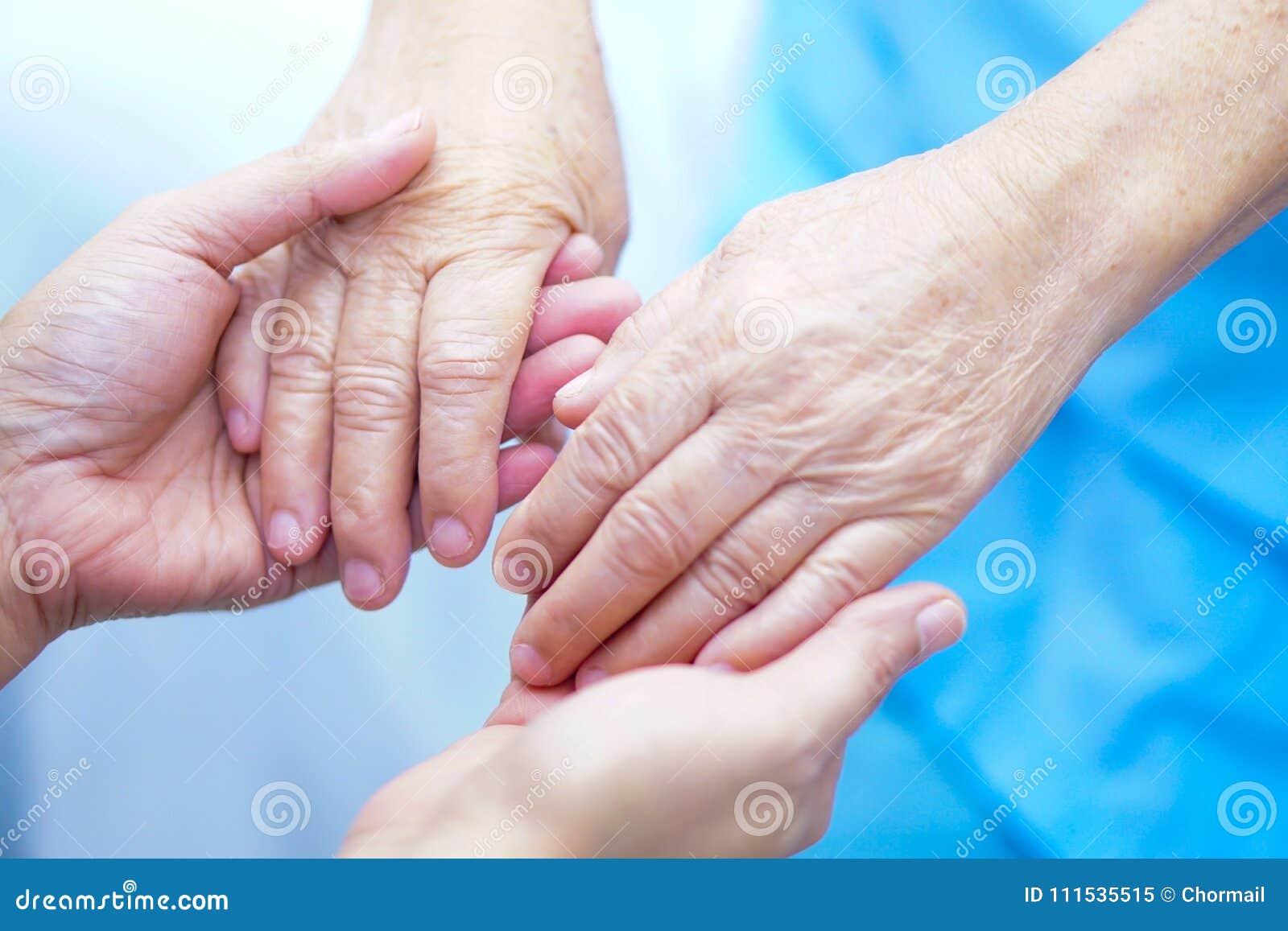 Держать старшего рук азиатского или пожилого пациента женщины пожилой женщины с влюбленностью, забота, ободряет и сопереживание н
