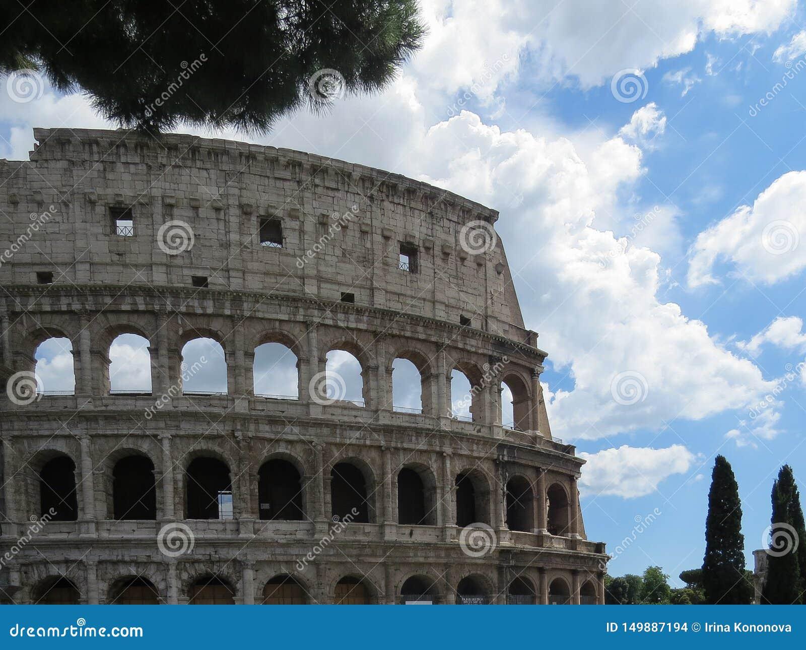 Детальный взгляд внешней стены Colosseum в Риме против голубого облачного неба