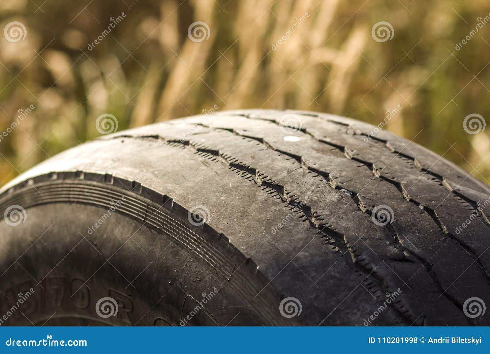 Деталь конца-вверх автошины колеса автомобиля плохо несенной и облыселой из-за отслеживать бедных или выравнивания колес
