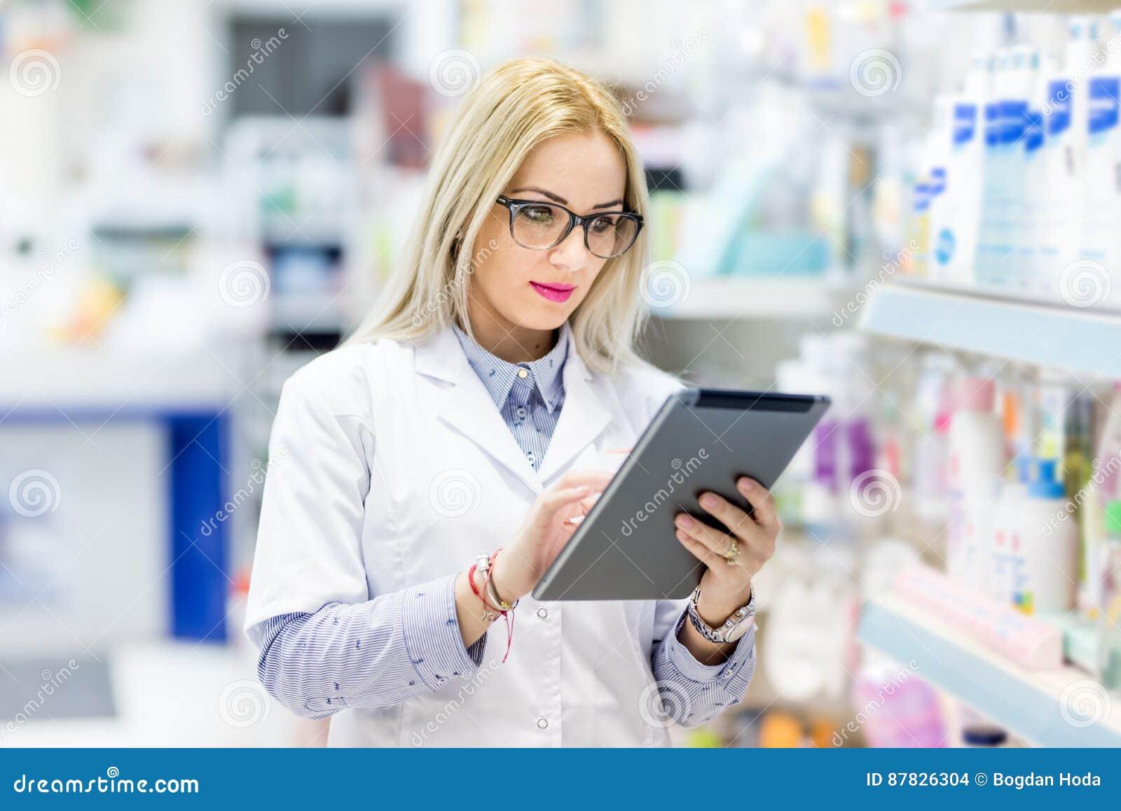 Детали фармации - доктор в белой форме используя таблетку и технология в фармацевтическом или медицинском поле