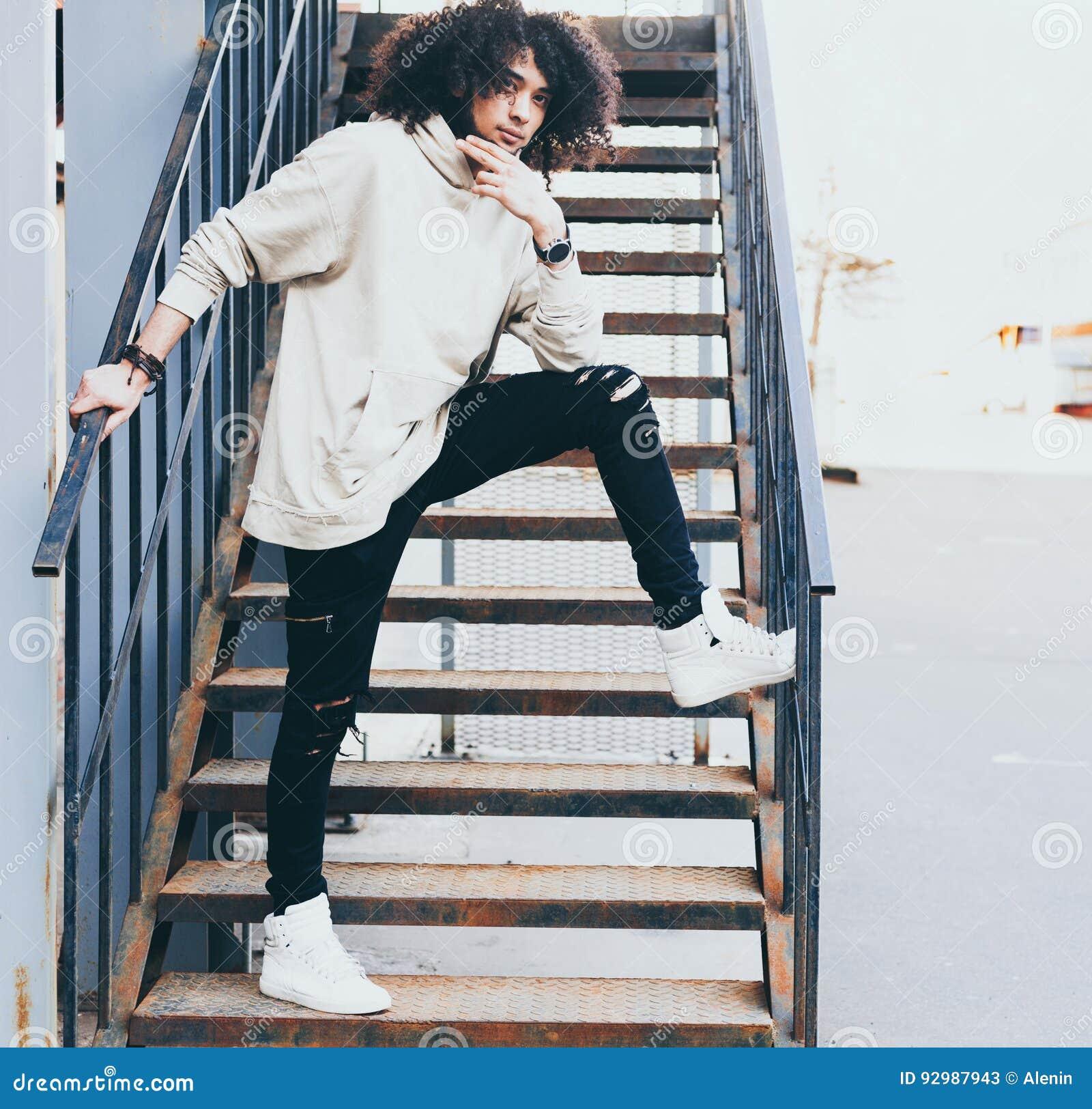 Детеныши модно одели человека в холодном обмундировании представляя на лестнице металла Волосы стиля Афро Streetstyle Мода молодо