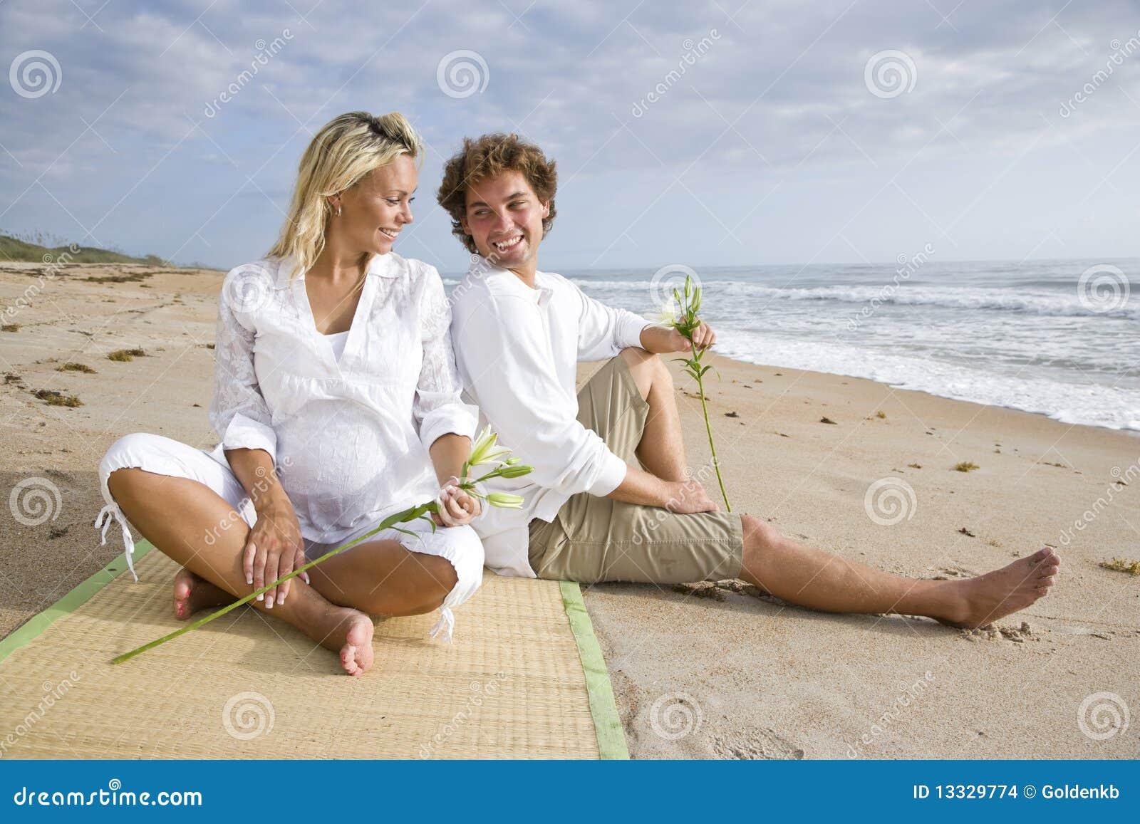 детеныши пар пляжа счастливые супоросые ослабляя