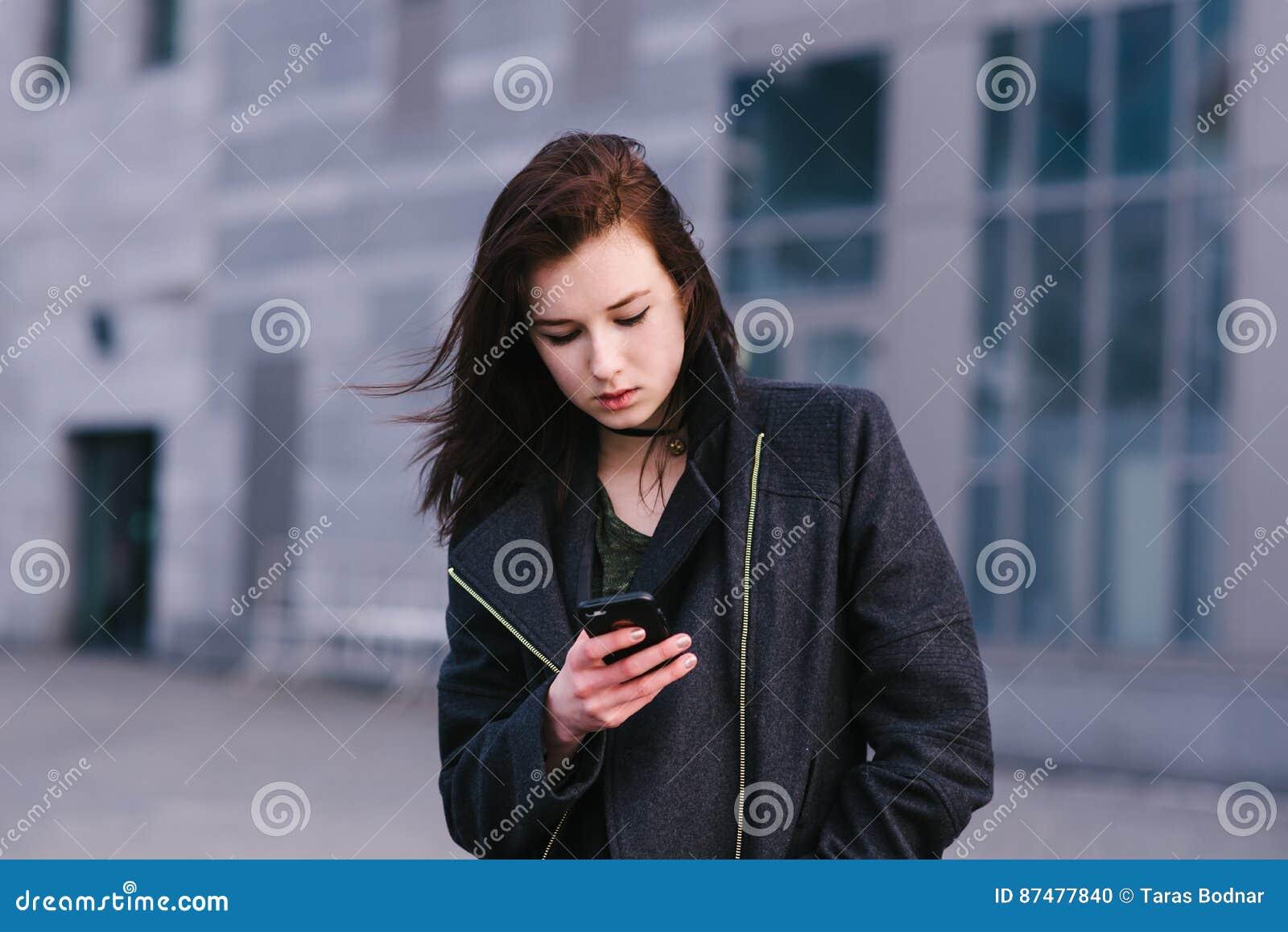 Детеныш и очень милая бизнес-леди брюнет используют мобильный телефон на предпосылке городского пейзажа