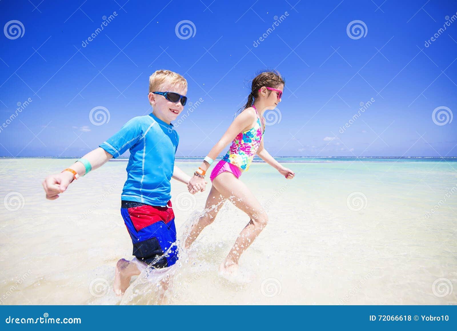 Дети брызгая в океане на тропическом пляже отдыхают