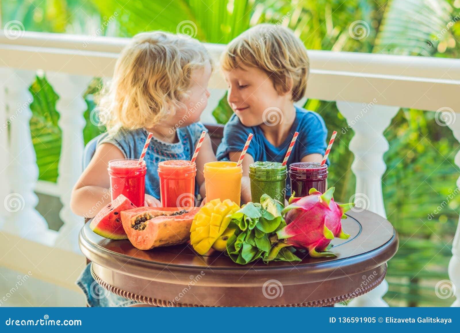Дети выпивают красочные здоровые smoothies Арбуз, папапайя, манго, шпинат и дракон приносить Smoothies, соки