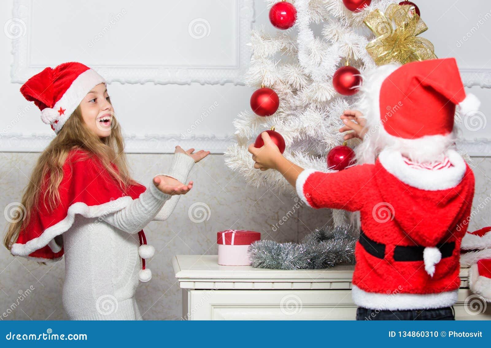Дети в шляпах santa украшая рождественскую елку Концепция традиции семьи Дети украшая рождественскую елку совместно