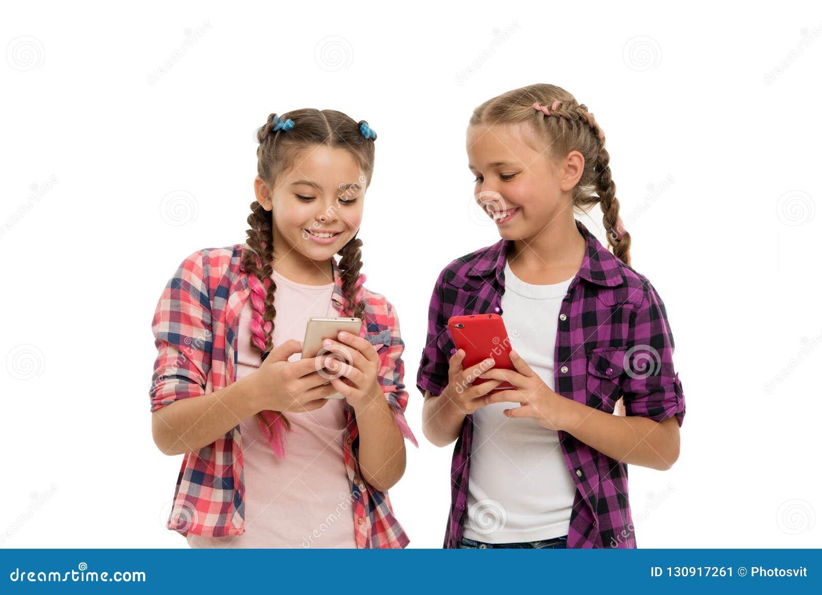 Дети девушек милые небольшие усмехаясь для того чтобы позвонить по телефону экрану Они любят сети интернет-серфинга социальные Пр