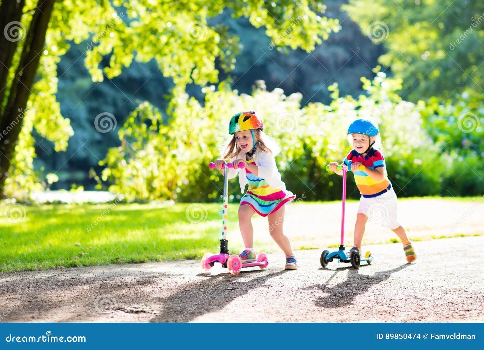 Дети ехать самокат в парке лета